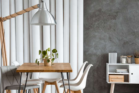 Wood and metal hairpin table standing under oversize lamp in bright interior with white tubes