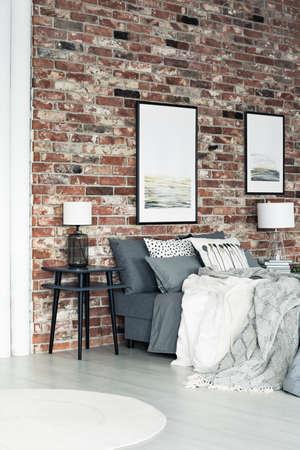 Zwei Poster hängen an einer Backsteinmauer im Loft Stil Schlafzimmer mit Lampe am Nachttisch Lizenzfreie Bilder
