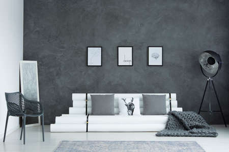 Three minimal modern posters hanging on raw grey wall in living room with studio lamp