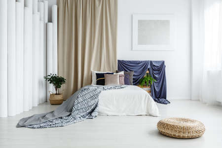 Pouf on the floor in bright bedroom with beige and blue satin cloths behind king-size bed and plants