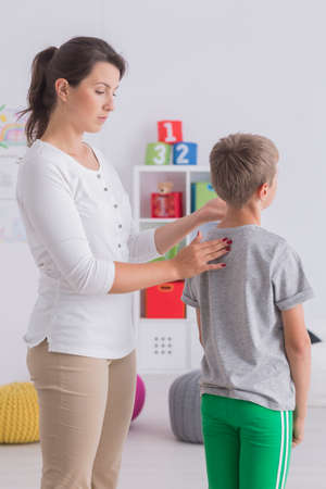 Child physiotherapy, female therapist working with little boy with scoliosis checking his spine condition