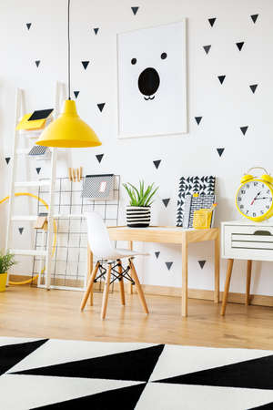 Yellow clock on white cabinet next to wooden desk and white chair in contrast color kindergarten Stock fotó - 89836999