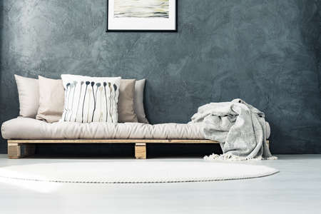 Helle Matratze gesetzt auf eine hölzerne Palette, die im Schlafzimmer mit rundem Teppich und roher grauer Wand steht