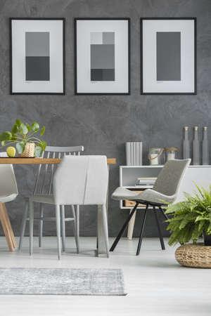 Graue Stühle, die einen Holztisch im Esszimmer mit den monochromen Plakaten stehen, die an einer strukturierten Wand hängen