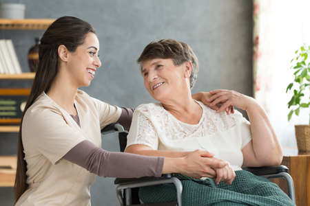 Friendly caregiver woman hugging smiling senior woman in wheelchair during visit at home Banco de Imagens