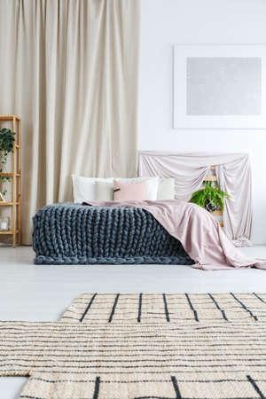 Weißes Schlafzimmer mit asymmetrischem Teppich, Silbermalerei an der Wand und Vorhang hinter dem Bett mit gestrickter Decke und rosa Bettdecke