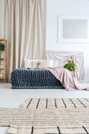 White bedroom with asymmetric carpet, silver painting on the wall and curtain behind bed with knit blanket and pink coverlet Stock Photo
