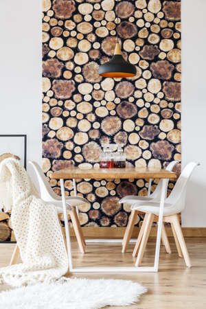 Table with white chairs, blanket and wallpaper with wood on the wall behind