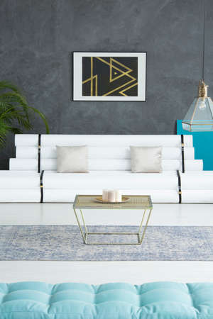 Two pillows placed on white paper tubes in bright sitting room with poster Lizenzfreie Bilder