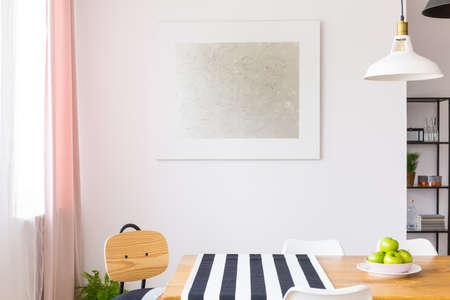 아파트 내부의 흰 벽에 창문과 나무 식탁 위에 매달려있는 우아한 그림 스톡 콘텐츠
