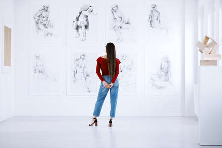 Fashionable woman looking at a display of paintings of female nudity in an art museum