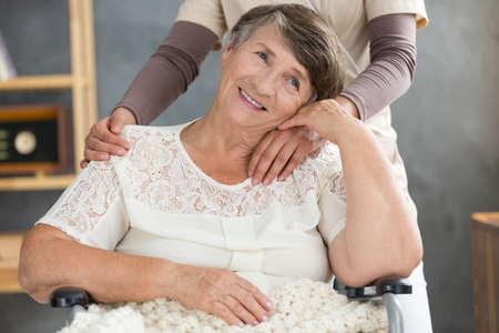 白いシャツで幸せな年配の女性は自宅でフレンドリーな人と時間を過ごします