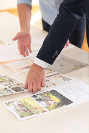 Nahaufnahme von den Leuten, die Fotos von Häusern für Verkauf in der Immobilienagentur betrachten
