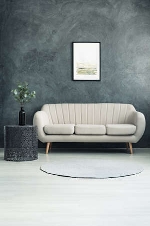 Bright couch standing in living room with grey textured wall and twigs with leaves in a glass vase on metal table Stock Photo