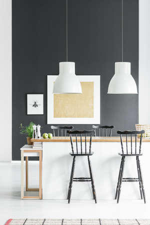 White lamps above kitchenette with rustic bar stools in dining room with plant