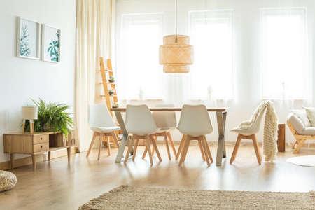 Varen en lamp op houten kast in heldere eetkamer met deken op witte stoel en rotanlamp boven lijst