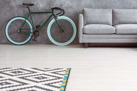 Trendy gray sofa and green bicycle with turquoise wheels in minimalist simple living room interior with copy space
