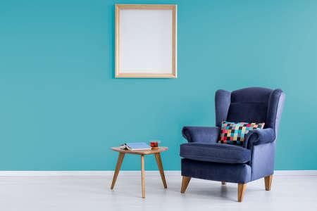 Libro con tapa azul y taza de té en una mesa pequeña en la sala de lectura con sillón Foto de archivo - 89908653