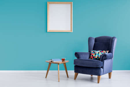 Book with blue cover and cup of tea on small table in reading room with armchair