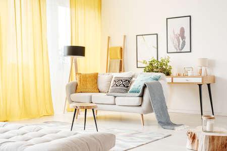 ソファ、マットレス付きの居心地の良いリビング ルームでポスターを壁にカーペットにテーブルの上に枕と毛布