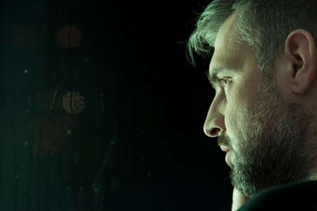 Close-up of depressed mans face against black background