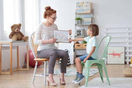 Professional family counselor helping young child to cope with his parents' divorce, showing him a drawing of a house Stockfoto