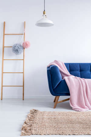 Wooden ladder with two tulle pompoms and white lampshade hanging above navy blue couch