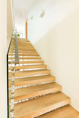 Houten trap naar de eerste verdieping met metalen leuning Stockfoto