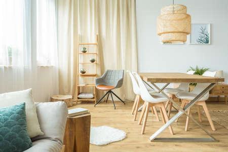Lámpara de ratán encima de la mesa y sillas en el comedor multifuncional con sofá y póster en la pared