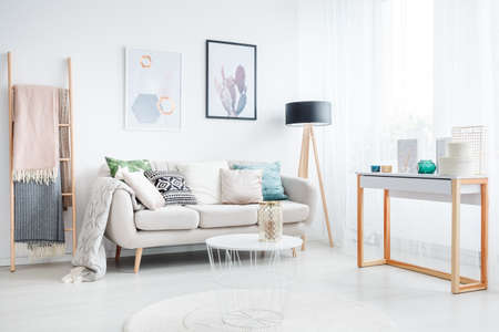 Blankets on a ladder and white table on a carpet in living room with lamp and cushions on a sofa Reklamní fotografie