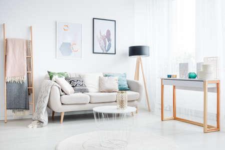 Dekens op een ladder en een witte lijst aangaande een tapijt in woonkamer met lamp en kussens op een bank Stockfoto