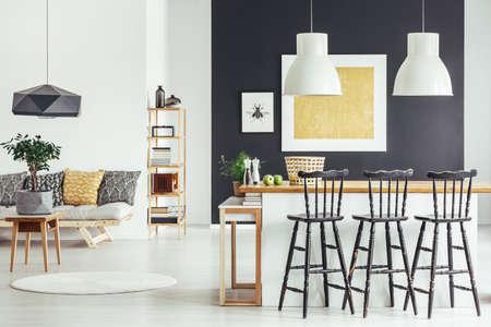 Schwarze Barhocker auf Kücheninsel und Sofa mit Kissen in geräumigem Innenraum im rustikalen Stil Standard-Bild - 89908682