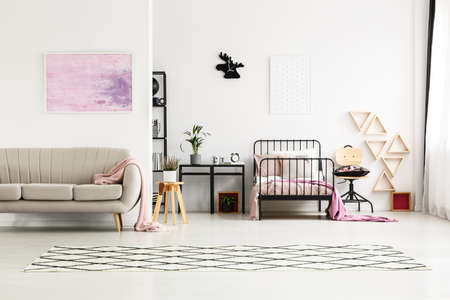 Pink painting above beige sofa in multifunctional girls bedroom with moose clock above bed and cabinet