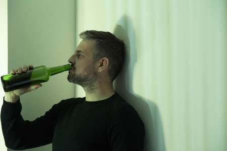 Depressed man drinking wine at home during mourning period