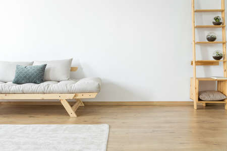枕と長いすに近い木製の棚の装飾とベージュのリビング ルームで白い壁や床にカーペットのスペースをコピーします。 写真素材