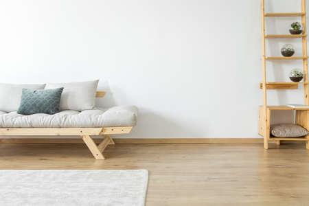 Copie o espaço da parede branca e tapete no chão na sala de estar bege com decoração em prateleiras de madeira perto de um sofá com travesseiros