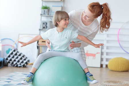 Physical therapist assisting little boy sitting on gym ball during rehabilitation in children hospital