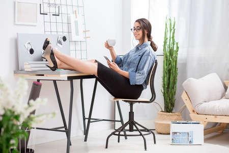 Mooie jonge dame in glazen koffie drinken en haar telefoon controleren tijdens pauze