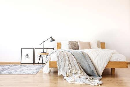 Beddengoed op houten kingsize bed tegen witte muur in ruime slaapkamer met lamp op een krukje