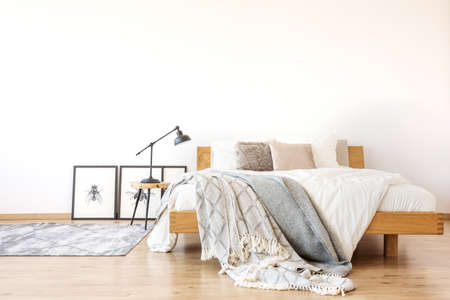 Bedsheets on wooden king-size bed against white wall in spacious bedroom with lamp on a stool