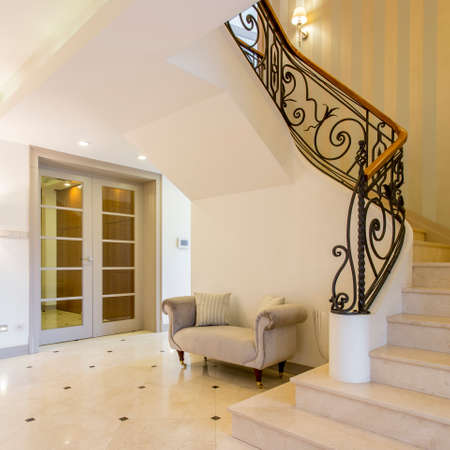 Light luxurious hallway with glossy tiles and beautiful staircase in elegant mansion