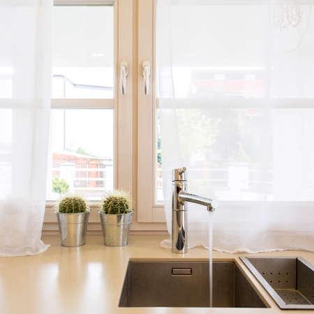 Minimalistische Küchenspüle mit Stahlhahn vor großem Fenster mit weißen Vorhängen