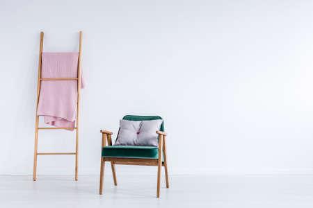 空の壁と椅子の部屋に木製のはしごに掛かっているピンクの毛布