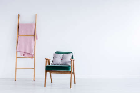 Pink blanket hanging on wooden ladder in room with empty wall and armchair Фото со стока