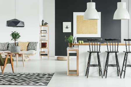 Black designer lamp above table with plant in pot in stylish living room with gold painting on wall