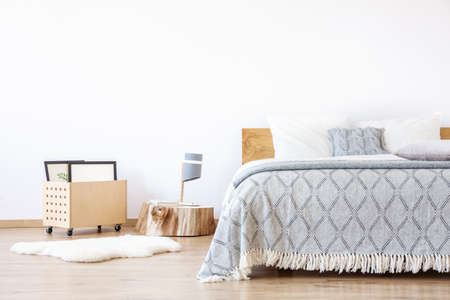 Designer lamp on wooden stump and white rug in simple bedroom with blue blanket on king-size bed