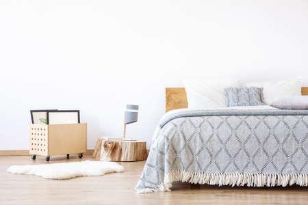 Designlamp op houten stronk en wit kleed in eenvoudige slaapkamer met blauwe deken op kingsize bed
