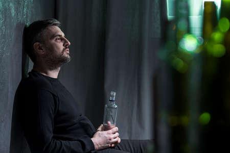 Sad man with alcohol addiction sitting alone and drinking vodka