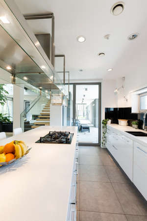 View of the white kitchen countertop with fruit and stairs