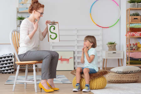 Cute little child with speech impediment and smiling young preschool teacher learning the alphabet letters in kindergarten classroom Stock Photo